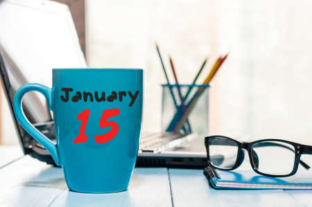 fifteen: January 15th. Day 15 of month, Calendar on cup morning coffee or tea, workplace background. Stock Photo