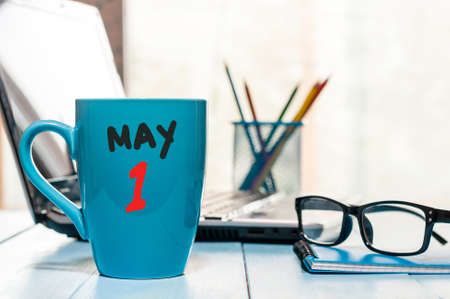 May 1st. Day 1 of month, calendar on morning coffee cup, business office background, workplace with laptop and glasses.