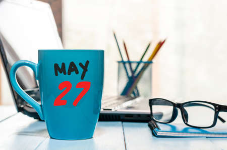 May 27th. Day 27 of month, calendar on morning coffee cup, business office background, workplace with laptop and glasses. Stock Photo
