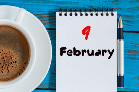 9th: February 9th. Day 9 of month, calendar in notepad on wooden background near morning cup with coffee.