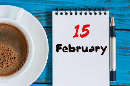 15th: February 15th. Day 15 of month, calendar in notepad on wooden background near morning cup with coffee. Stock Photo