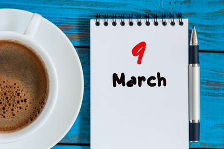 9th: March 9th. Day 9 of month, calendar on blue wooden table background with morning coffee cup. Spring time, Top view. Stock Photo