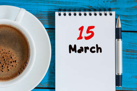15th: March 15th. Day 5 of month, calendar on blue wooden table background with notepad and morning coffee cup. Spring time, Top view.