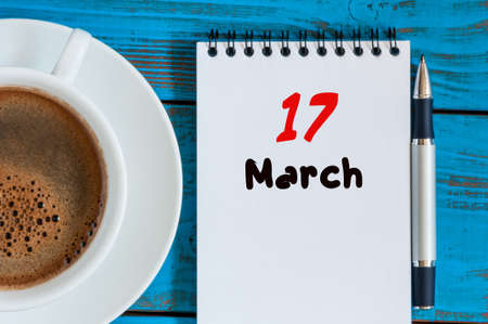march 17th: Happy St Patricks Days save the date. March 17th. Day 17 of month, calendar on blue wooden table background with morning coffee cup. Spring time, Top view.