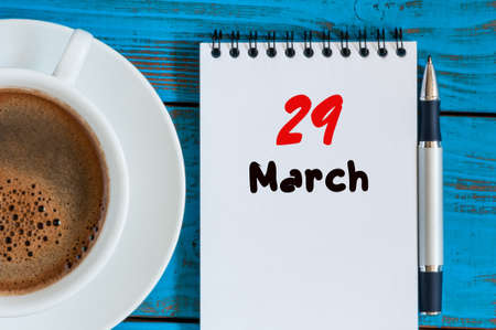 nine years old: March 29th. Day 29 of month, calendar on blue wooden table background with morning coffee cup.
