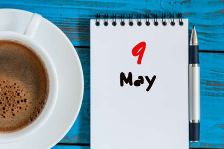 9th: May 9th. Day 9 of month, calendar on white notepad with morning coffee cup at work place background.