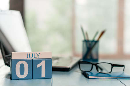 July 1st. Day of the month 1 , wooden color calendar on workplace background.