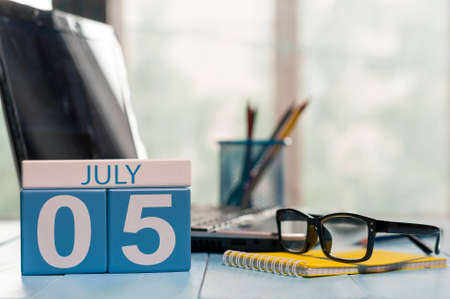 July 5th. Day of the month 5 wooden color calendar on business workplace background.