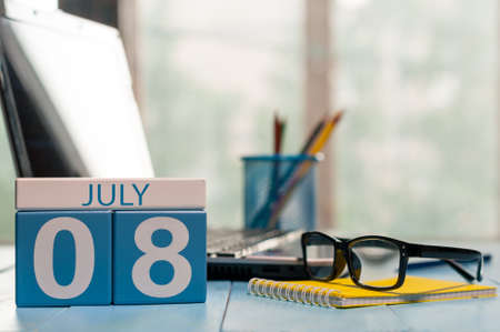 important date: July 8th. Day 8 of month, wooden color calendar on freelance workplace background.