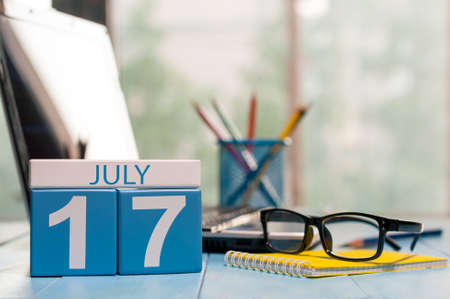 17th: July 17th. Day 17 of month, wooden color calendar on workplace background. Stock Photo