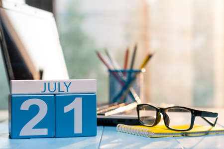 next year: July 21st. Day 21 of month, wooden color calendar on office workplace background.