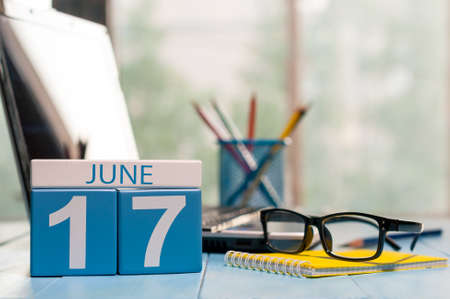 17th: June 17th. Day 17 of month, wooden color calendar on workplace background. Stock Photo