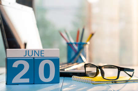 June 20th. Day 20 of month, wooden color calendar on workplace background.