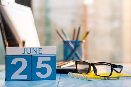 June 25th. Day 25 of month, wooden color calendar on workplace background. Stock Photo