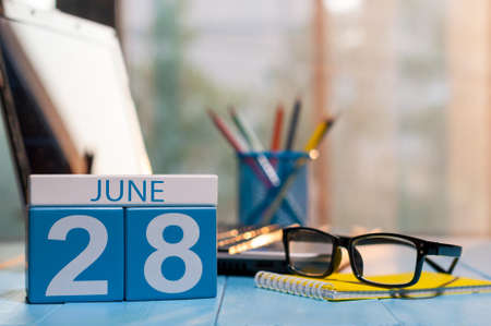 June 28th. Day 28 of month, wooden color calendar on workplace background. Stock Photo