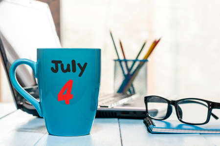 July 4th. Day of the month 4 , color calendar on morning coffee cup at workplace background.
