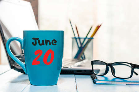 20th: June 20th. Day 20 of month, color calendar on morning coffee cup at business workplace background.