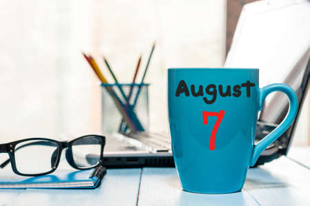 August 7th. Day 7 of month, morning coffee cup with calendar on business background.