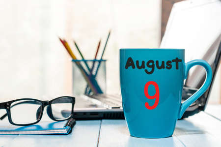 9th: August 9th. Day 9 of month, morning coffee cup with calendar on business office background.