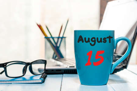 fifteen: August 15th. Day 15 of month, morning coffee cup with calendar on freelance workplace background.