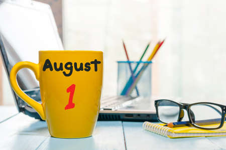August 1st. Day of the month 1, morning yellow coffee cup with calendar on business workplace background. Summer time. Empty space for text.
