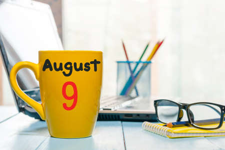 August 9th. Day 9 of month, morning yellow coffee cup with calendar on workplace background.
