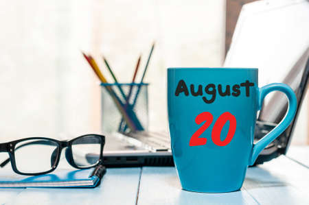 20th: August 20th. Day 20 of month, morning coffee cup with calendar on workplace background.