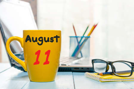 August 11th. Day 11 of month, morning yellow coffee cup with calendar on freelance workplace background. Summer time. Empty space for text. Stock Photo
