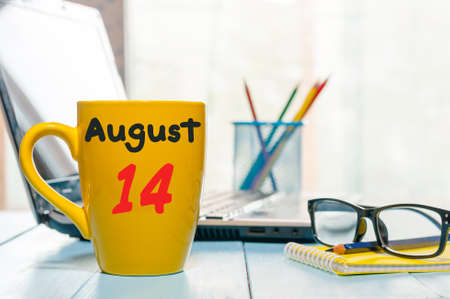 August 14th. Day 14 of month, morning yellow coffee cup with calendar on workplace background. Stock Photo