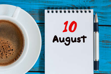 10th: August 10th. Day 10 of month, loose-leaf calendar on blue background with morning coffee cup. Stock Photo
