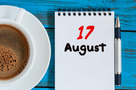 looseleaf: August 17th. Day 17 of month, loose-leaf calendar on blue background with morning coffee cup.