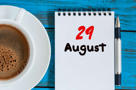 looseleaf: August 29th. Day 29 of month, loose-leaf calendar on blue background with morning coffee cup. Summer time. Top view.
