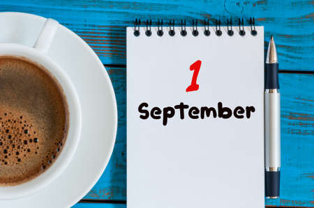 September 1st. Day 1 of month, loose-leaf calendar on blue background with morning coffee cup. Autumn time. Empty space for text. Back to school. Standard-Bild