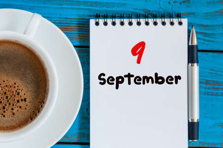 september 9th: September 9th. Day 9 of month, coffee or tea cup with loose-leaf calendar on blue background
