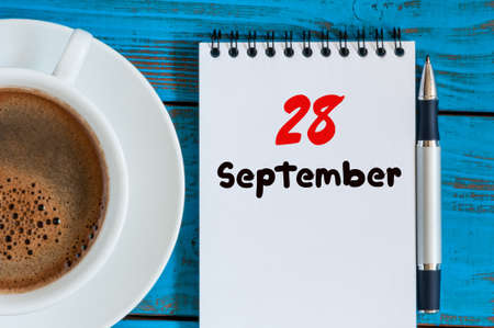 looseleaf: September 28th. Day 28 of month, morning coffee cup with loose-leaf calendar on blue background