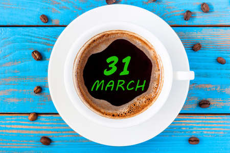 31st: March 31st. Day 31 of month, calendar written on morning coffee cup at blue wooden background.