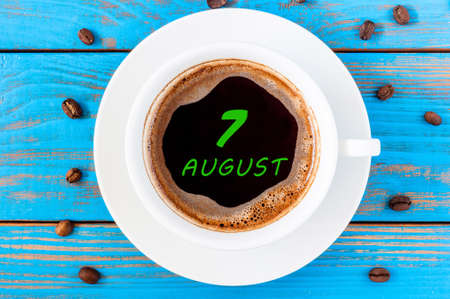 top 7: August 7th. Day 7 of month, morning coffee cup with calendar on drinks surface. Blue wooden background and beans. Top view. Stock Photo
