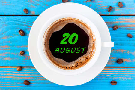 20th: August 20th. Day 20 of month, morning coffee cup with calendar on drinks surface. Blue wooden background and beans. Top view.