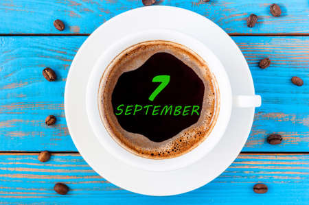 top 7: September 7th. Day 7 of month, calendar on morning coffee cup at blue workplace background. Autumn time, Top view.