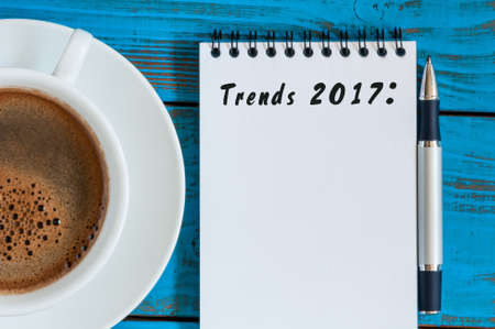 business trends: Trends 2017 written at notepad on blue table workplace near cup of morning coffee. New year business and fashion innovation.