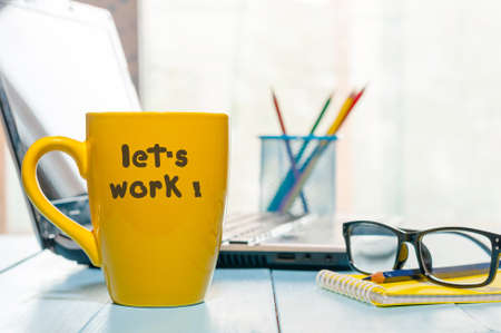 Lets work - business concept with text on yellow cup with morning coffee or tea. horizontal image. Stock Photo