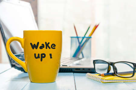 WAKE UP motivation text on cup with morning coffee or tea at office background or business workplace. Stock Photo