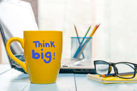 mindful: Inspirational saying Think big written on morning coffee cup at business office workplace. Empty space for text. Stock Photo