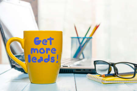 Get more leads motivation phrase on yellow cup of morning coffee or tea at business office workplace backgound. With empty space for text.