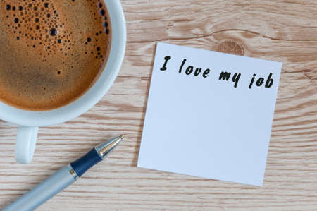 I love my job motivation inscription on peace of paper at workplace near morning coffee cup. With empty space for text.
