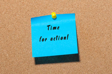 Time for Action written on blue sticker pinned to cork notice board. Stock Photo
