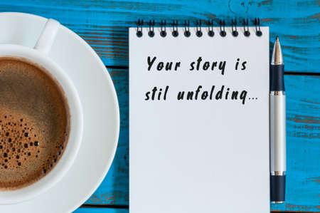Uw verhaal is nog in volle gang motivatie inscriptie op blocnote in de buurt van 's ochtends kopje koffie, Bovenaanzicht met lege ruimte.