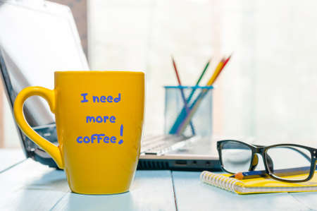 energy needs: I need more coffee written on big yellow cup with hot drink at home or business office workplace background. Stock Photo