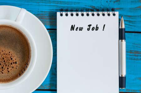 NEW JOB - opschrift in kladblok in de buurt van 's ochtends kopje koffie. Mogelijkheid, toeval of gelegenheid concept.