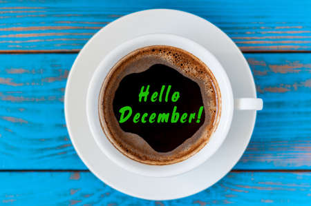 december 25th: Hello December written on coffee cup at blue wooden desk. Eve, Christmas and New year time concept.